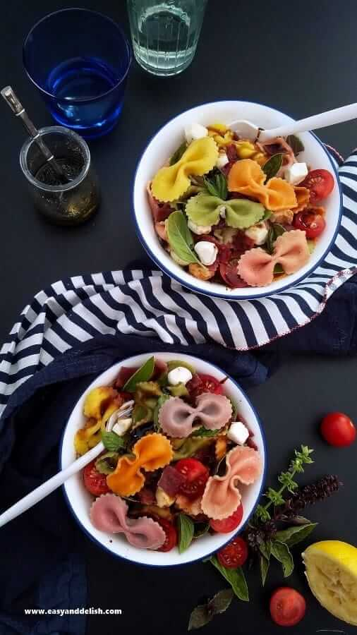 Two bowls of bacon caprese pasta salad on a table