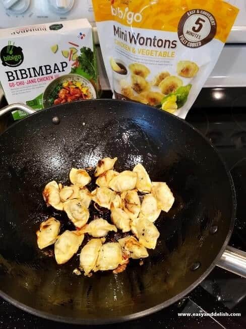 wontons being cooked in a wok