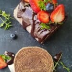 chocolate cake roll topped with berries and partially sliced