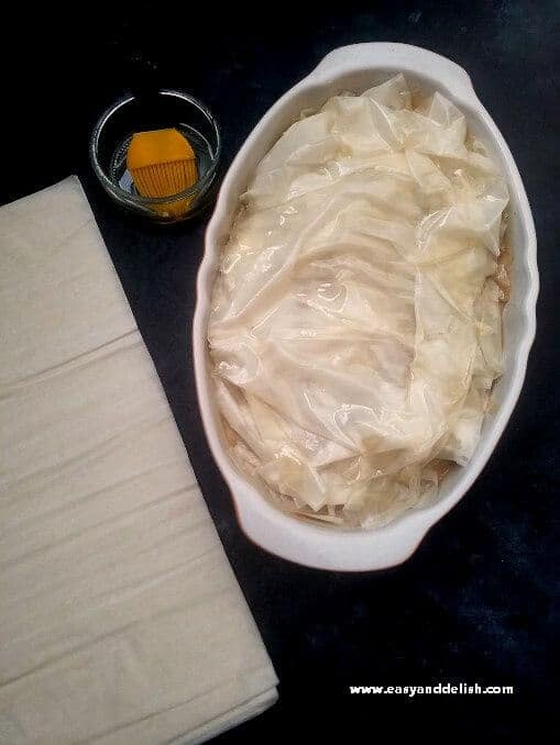 Oiling phyllo dough sheets for topping of Mediterranean chicken pot pie