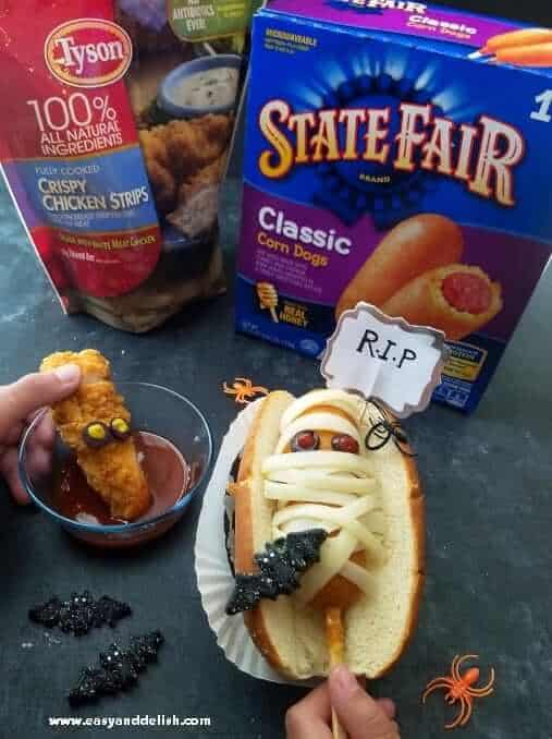 "Mummy coffin corn dogs and ""bloody chunky worm"" on a table"