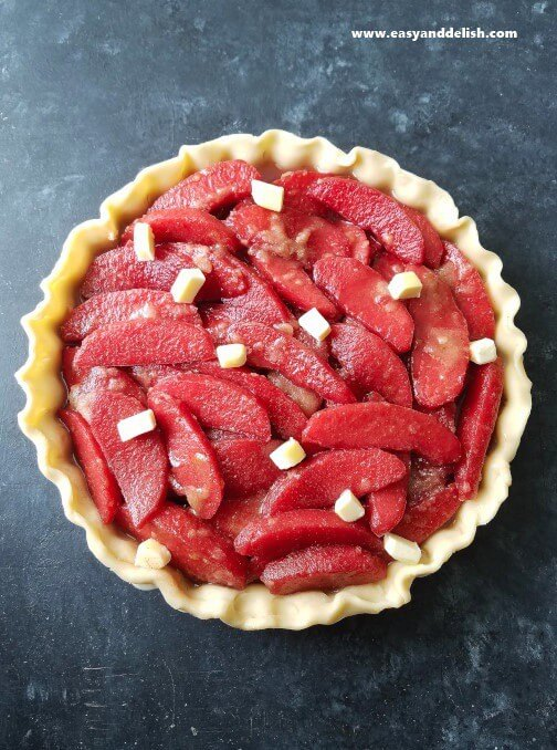 Cooking step for ruby apple pie showing colored apples into pie crust dotted on top with butter