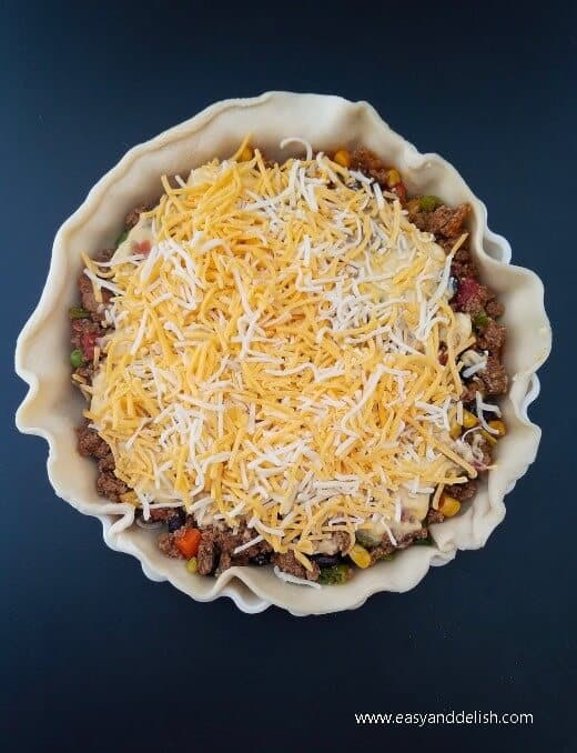 Layering shredded cheese over open chili bean turkey pot pie