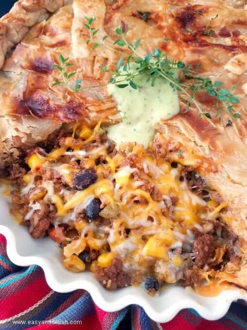 Close up image of chili bean turkey pot pie topped with guacamole sauce