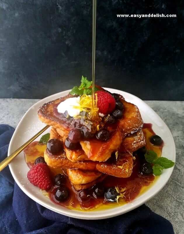 a plate with French toast piled up with a pouring of maple syrup
