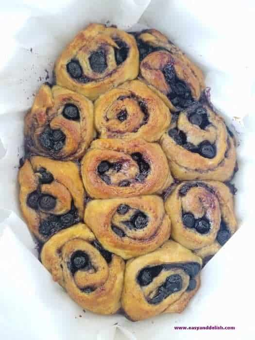baked blueberry pie cinnamon rolls in a baking pan before being frosted