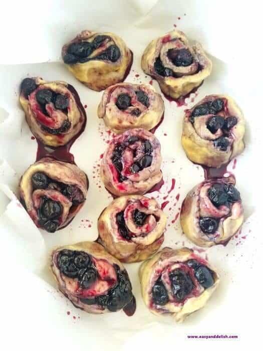 blueberry pie cinnamon rolls arranged in a baking pan before baking
