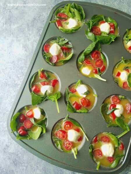 filling muffin tin to bake Caprese breakfast egg cups