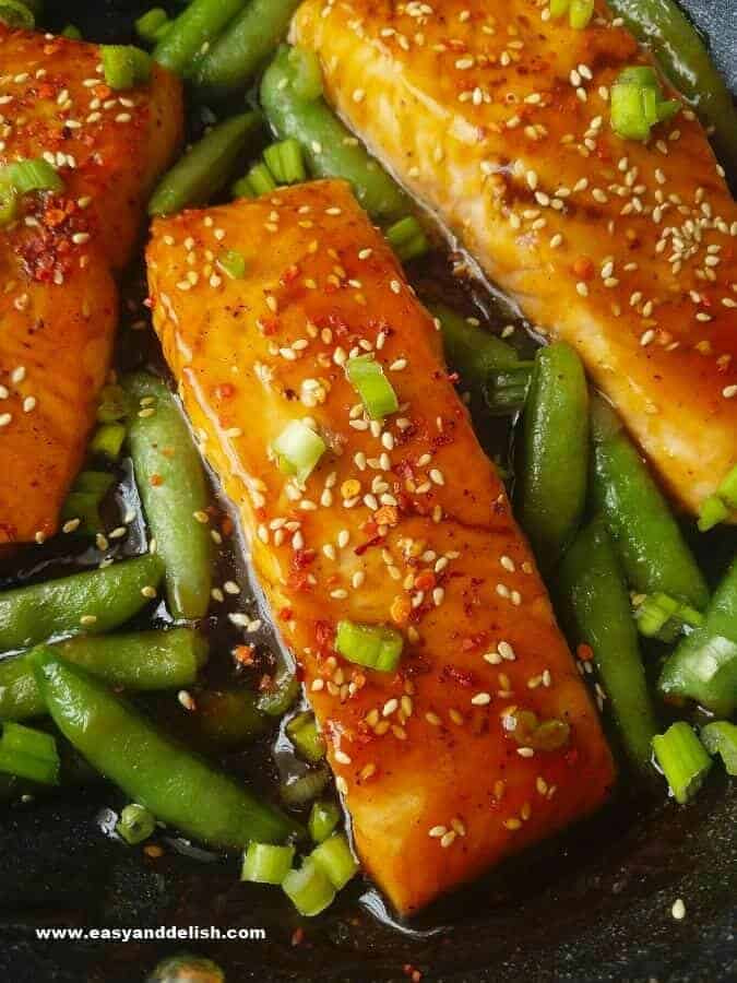 Close up image showing cooked sriracha teriyaki salmon fillets and snap peas in a pan
