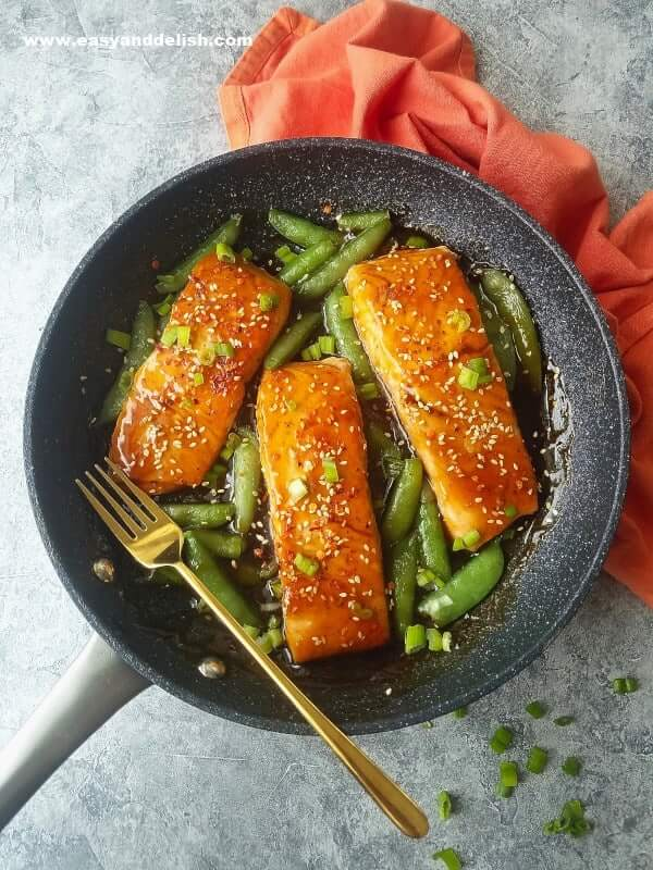 serving sriracha teriyaki salmon in a skillet