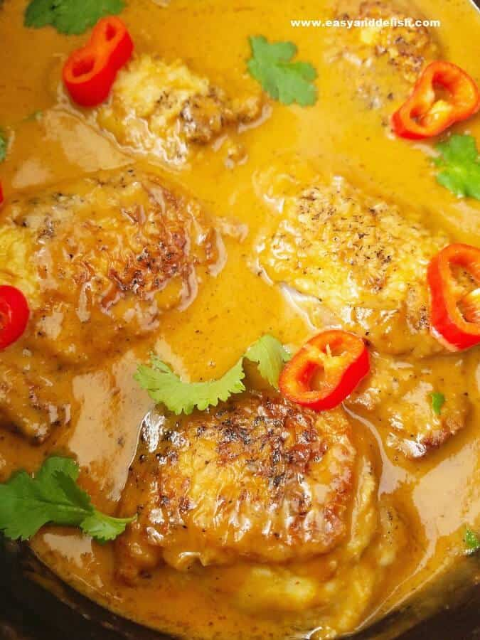 Close up image of cooked chicken satay curry in the slow cooker