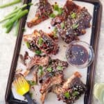 Chinese barbecue ribs in a baking sheet with green onions of the side and top