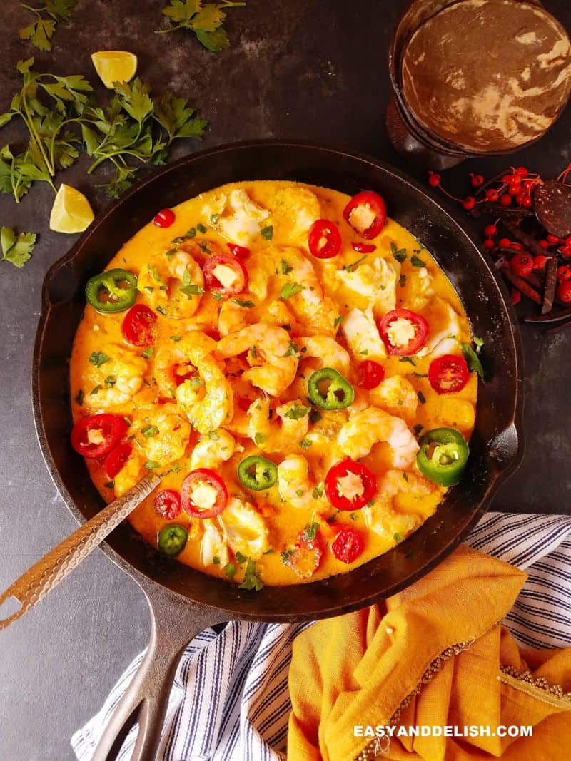 Brazilian moqueca in a pan with garnishes around
