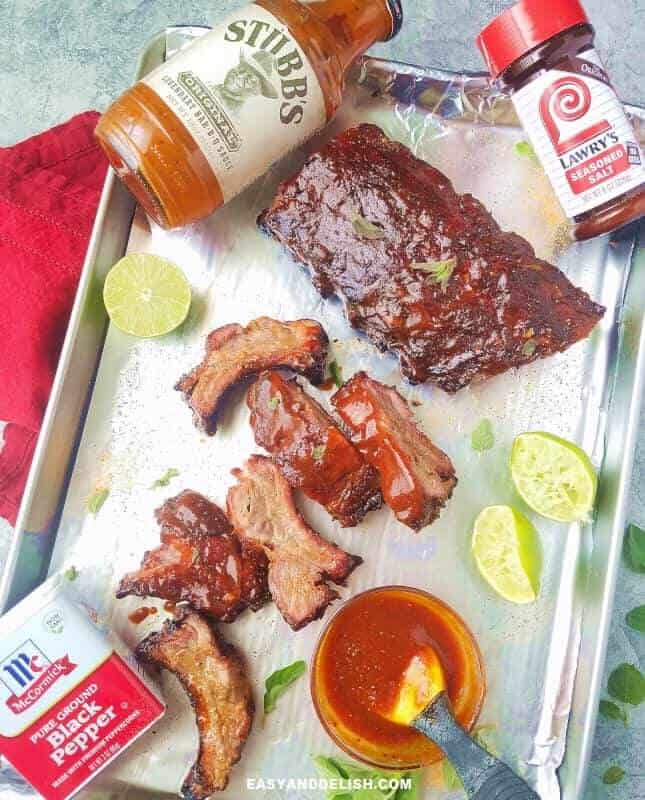 grilled barbecue pork ribs in a sheet pan with sauce, lime and herbs on the side