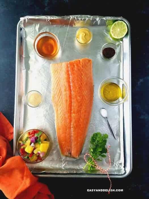 salmon fillet and other ingredients in a cookie sheet