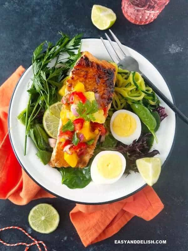 a plate with cooked salmon, greens, boiled eggs, and lime