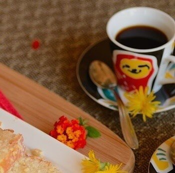 Table scene with a cup of coffee that has a smiling red and yellow sloth painted on it