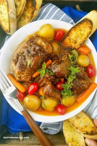 A bowl of beef Oxtail with veggies and bread on a tray