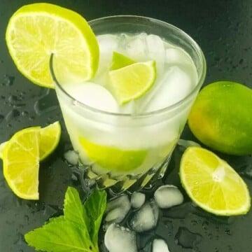 a glass of Caipirinha with lime wedges