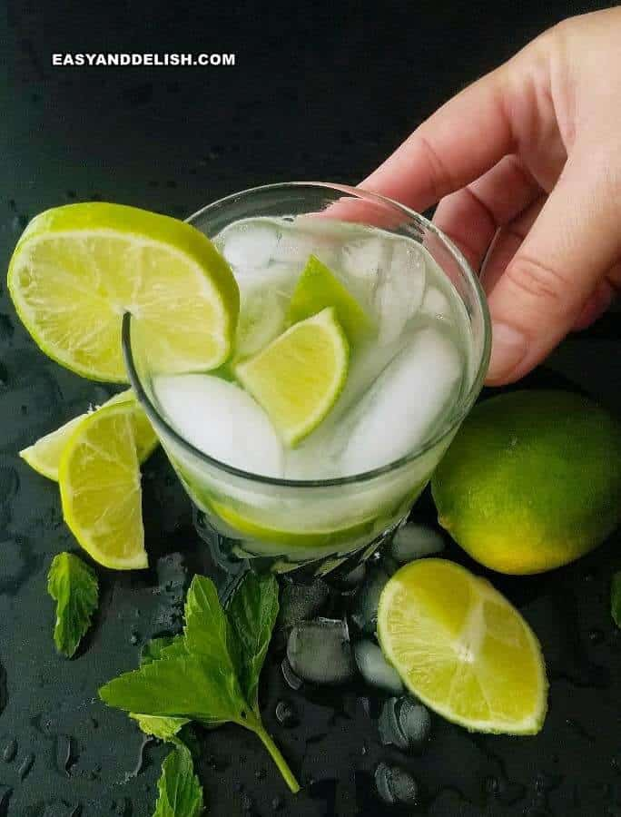 HAND REACHING A GLASS OF CAIPIRINHA DRINK