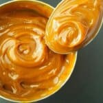 a can of homemade dulce de leche with a spoon