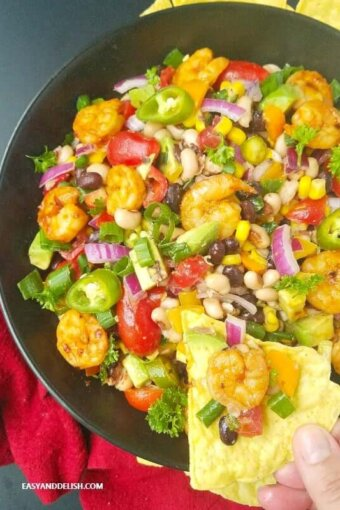 texas caviar recipe in a skillet with shrimp, avocado, and lime vinaigrette with tortilla chips.