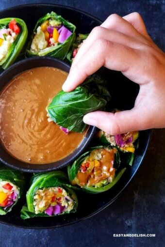 A bowl of collard green wraps with a small bowl of peanut sauce in the middle and one of them being dipped