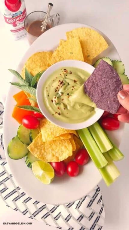 dipping a tortilla chip into a bowl of the best avocado dip