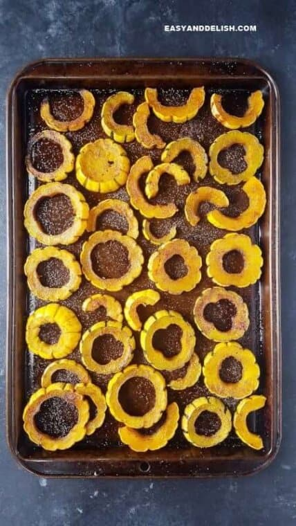 delicata squash in a baking sheet after being roasted