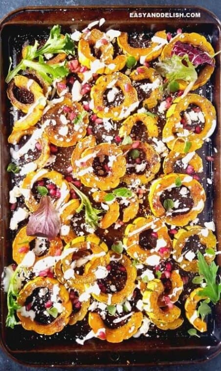 roasted delicata squash in a sheet pan beautifully garnished with yogurt, pomegranate seeds, and herbs