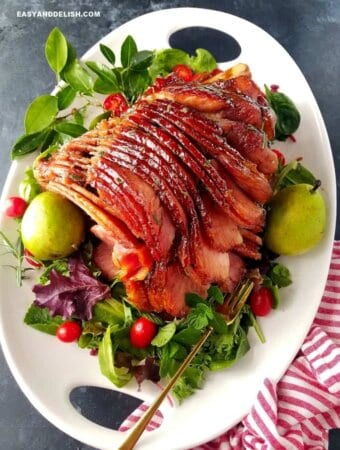 A platter with honey baked ham garnished with pears and veggies