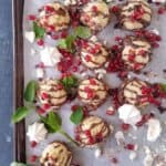 many low carb chocolate chip coconut cookies drizzled with melted chocolate and garnished with pomegranate seeds in a baking pan