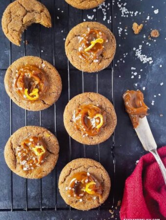 cinnamon cookies topped with dulce de leche over a rack with coarse salt sprinkles