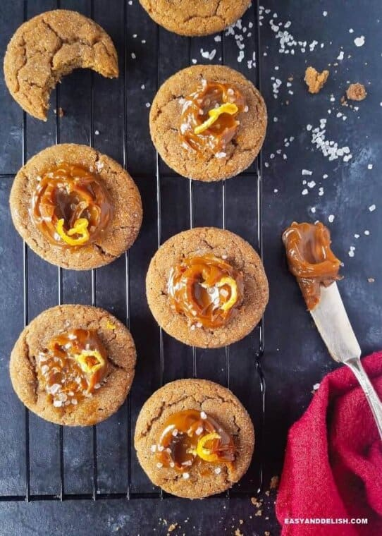 dulce de leche cookies on a rack with a spatula on the side