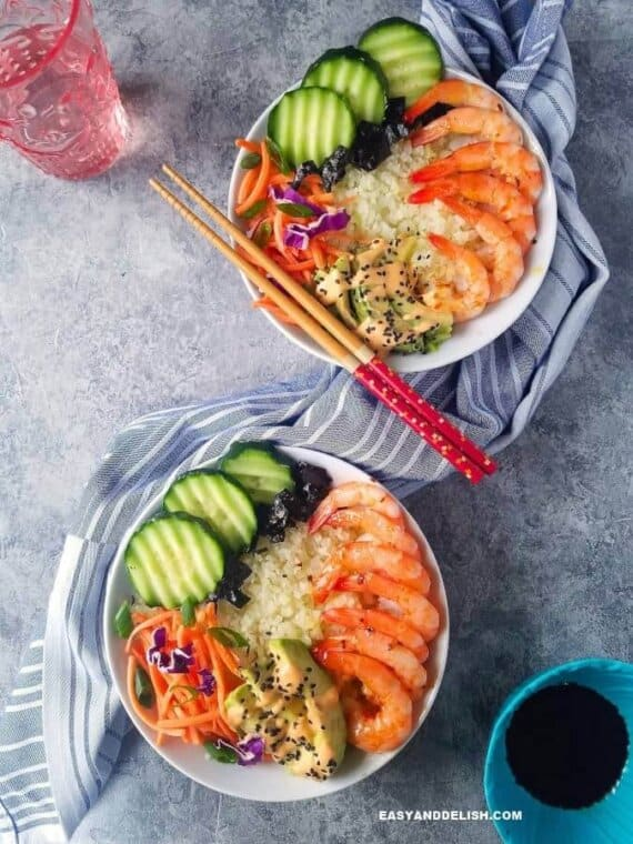 two sushi bowl with a glass of water and chopsticks on the side