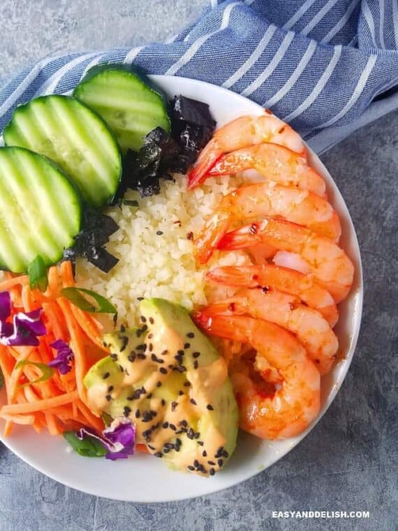 one sushi bowl with cauliflower rice, shrimp, avocado, cucumber, nori, carrots,a nd sriracha mayo.