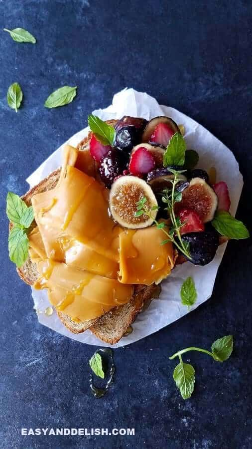 A toast topped with brown cheese or brunost and fruits