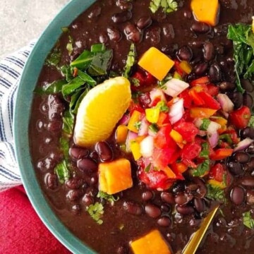 A bowl of vegetarian feijoada with garnishes on top