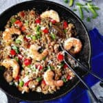 Cajun dirty rice with shrimp in a skillet and silveware on the side