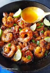 A skillet filled with shrimp and lime wedges