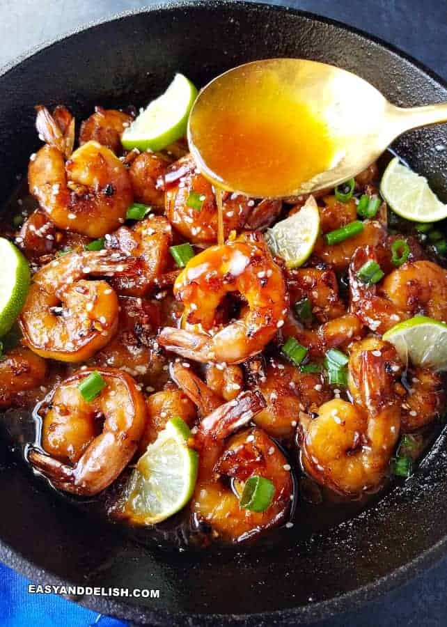 honey garlic butter shrimp in a skillet with sauce being poured from a spoon
