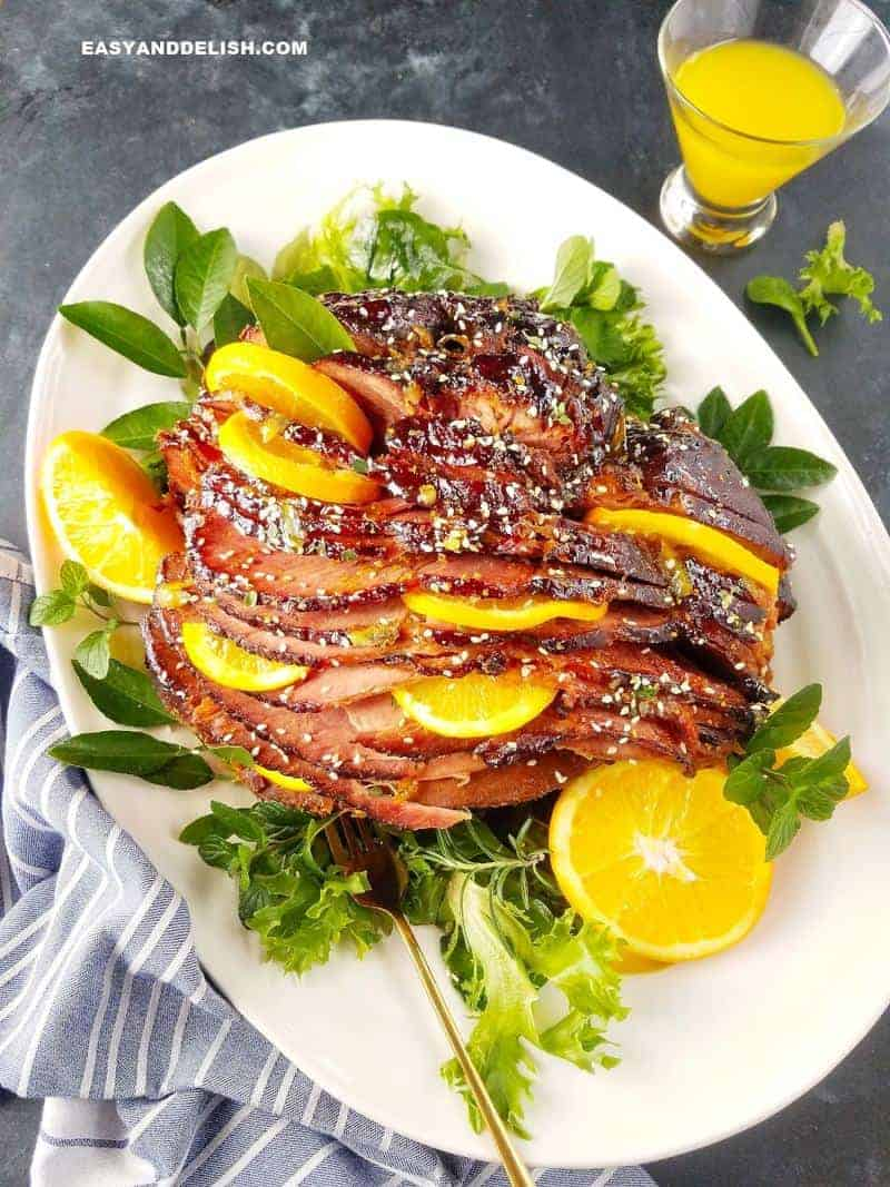 slow cooker orange glazed ham in a platter with orange slices