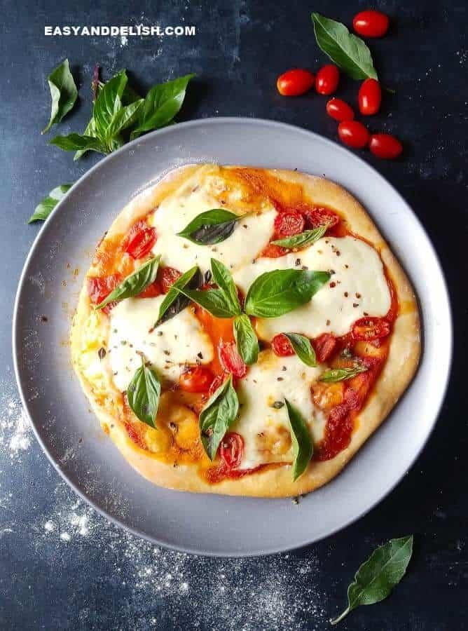 pizza marguerita com tomates e hervas ao lado