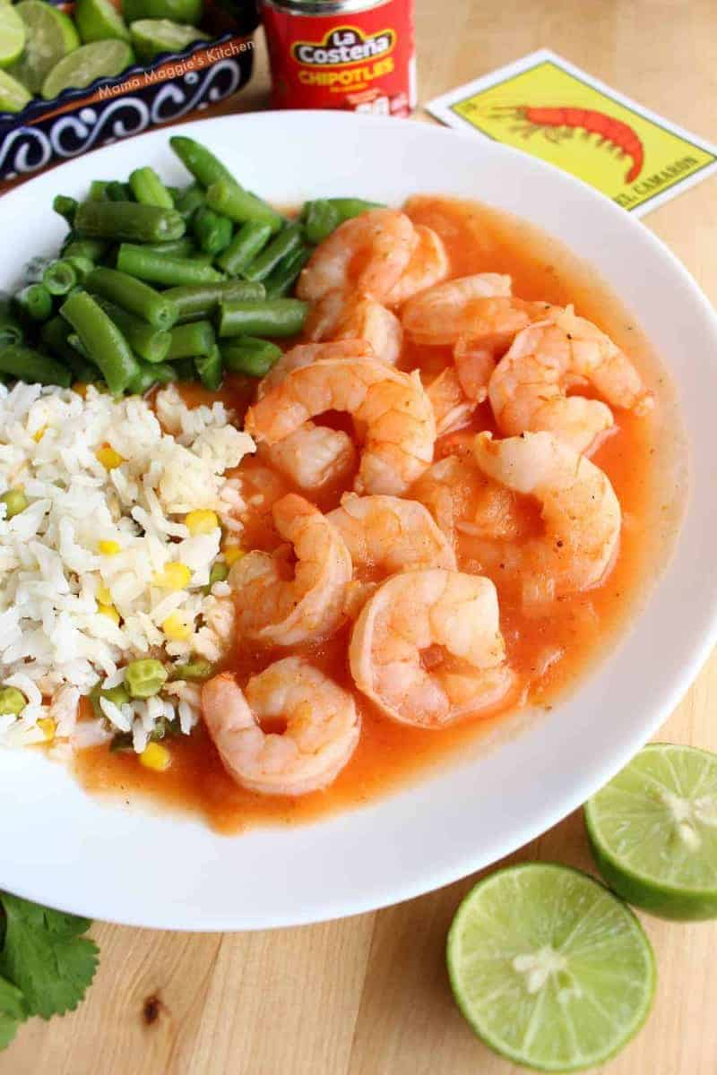 a plate of shrimp, rice and green beans with limes on the side