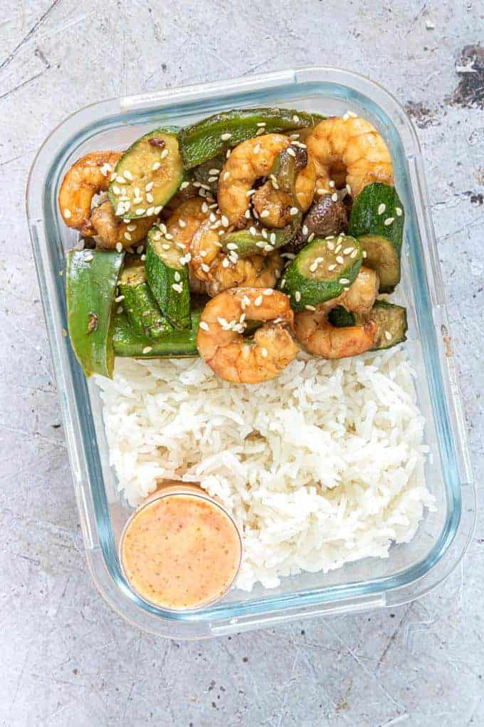 shrimp, vegetables and rice in a container with a bowl of sauce