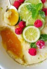 close up de bolo de limao com fatias de limao no topo e frutas vermelhas