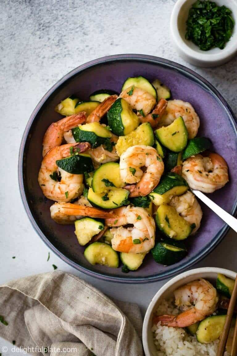 shrimp and zucchini in a bowl with ganishes on the side