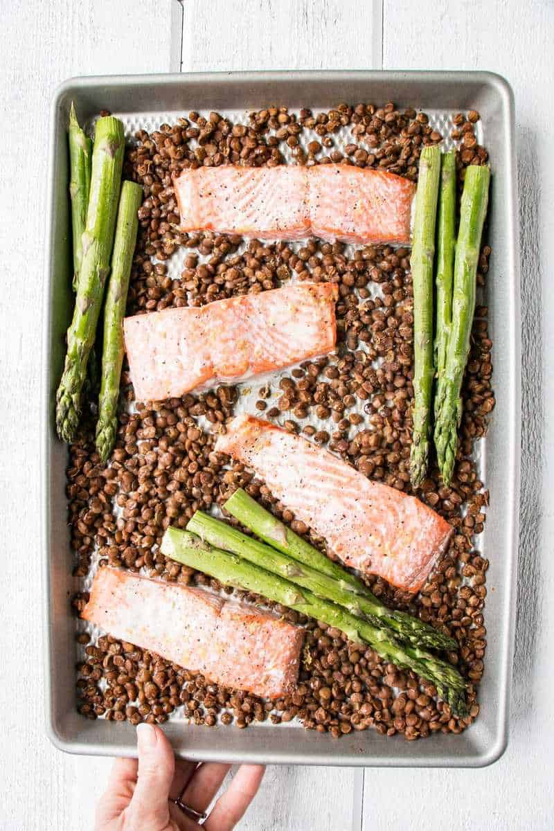 salmon , lentils and asparagus in a sheet pan with a hand holding it