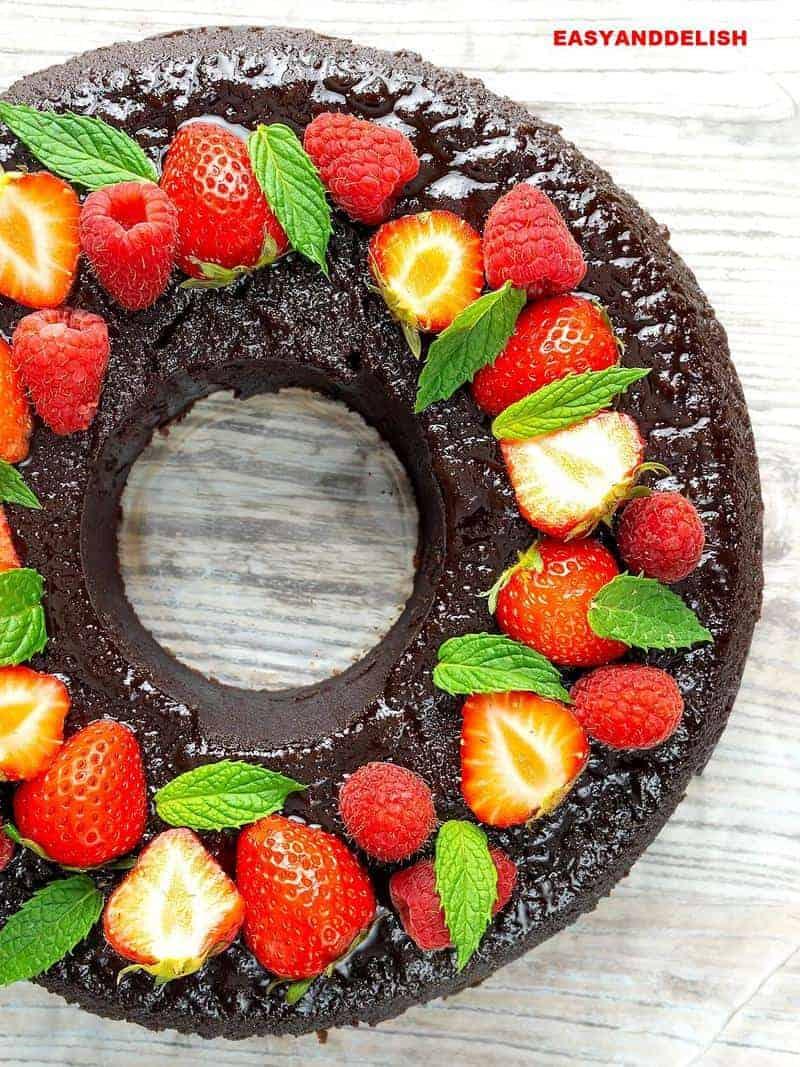 pudim de chocolate inteiro com frutas vermelhas no topo