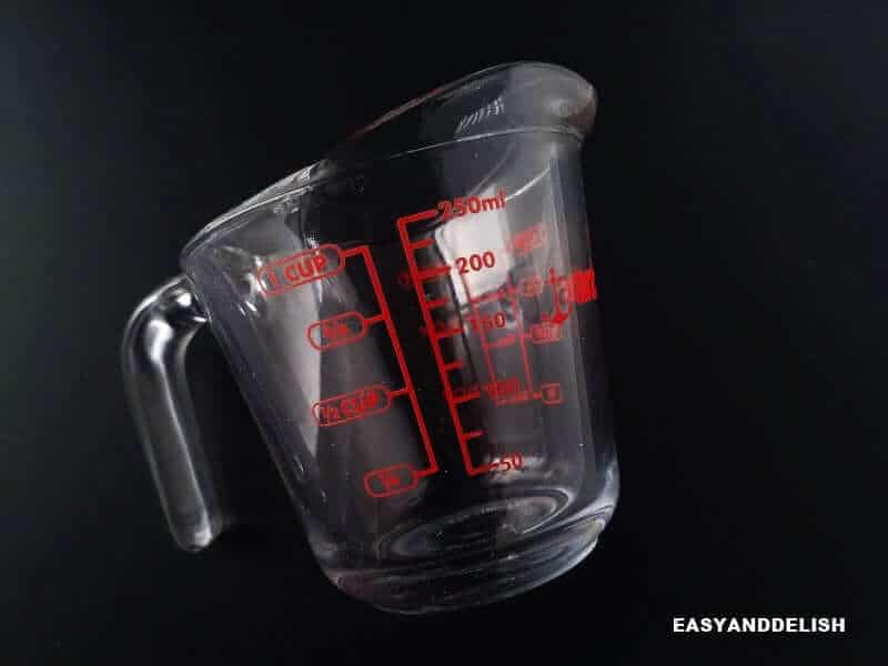 a measuring cup with marks in cups and milliliters for volume conversions and measurements